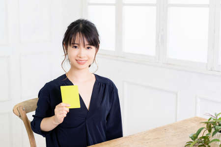 A young woman holding a yellow card shot in the studio