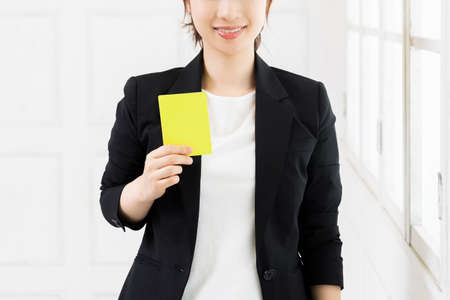 A young business woman holding a yellow card shot in the studio