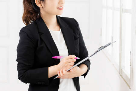 A young business woman writing notes on a clipboard taken in the studio