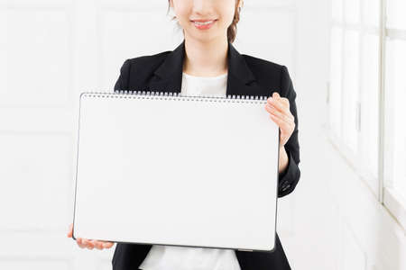 Young business woman with a large sketchbook taken in the studio Stock Photo