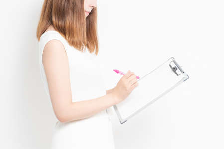 A young woman writing notes on a clipboard taken in the studio