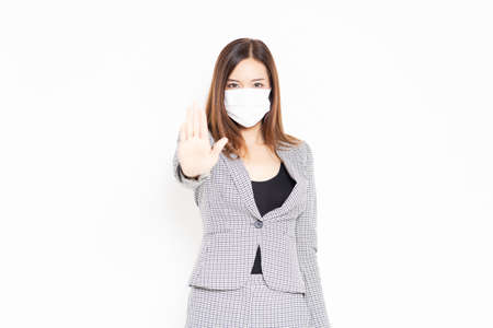 A masked business woman who makes NG gestures shot in the studio Imagens