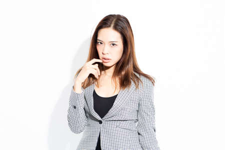 A young business woman standing and posing in front of a white background shot in the studio