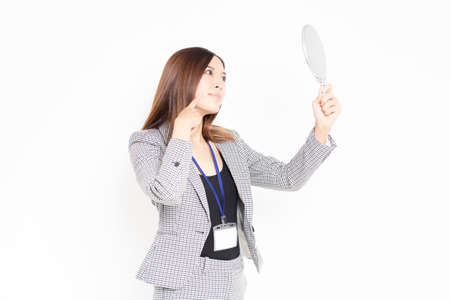 Business woman with a hand mirror taken in the studio