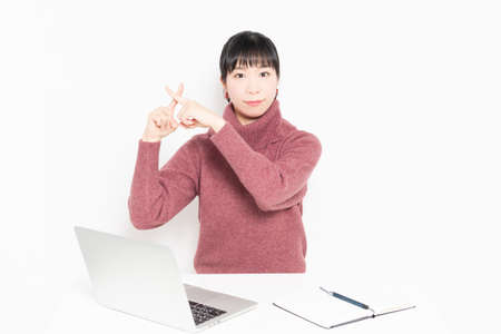 A woman making an NG gesture while using a laptop shot in the studio