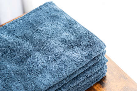 Blue face towel on a walnut table by the window