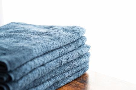 Blue face towel on a walnut table by the window 版權商用圖片
