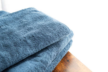 Blue face towel and bath towel on the walnut table by the window