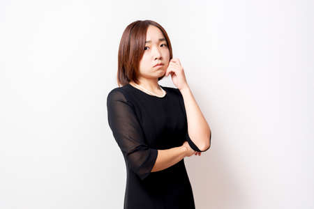 A woman in a mourning dress with a worried gesture, shot in the studio
