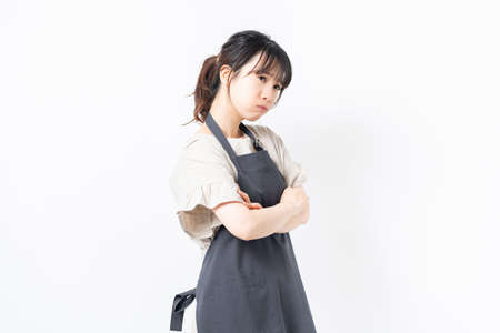 A young woman in an apron with her arms crossed, shot in the studio