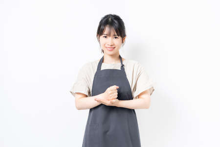 A young woman in an apron with a convincing gesture shot in the studio Foto de archivo