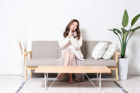 A young woman sitting on the sofa in the living room and making a request gesture, shot in the studio