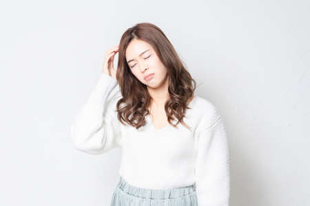 A young woman in the studio, standing in front of a white wall and worried 版權商用圖片