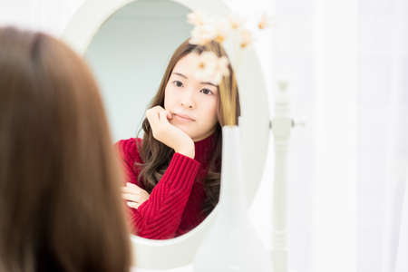 A young woman thinking in front of a mirror shot in the studio