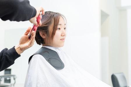 A young woman having her hair cut at a hair salon