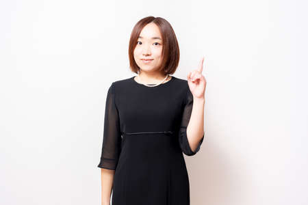 A woman in a mourning dress standing in front of a white background and showing points