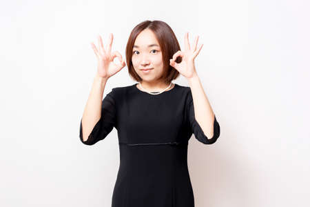 A woman in mourning dress standing in front of a white background and making an OK gesture