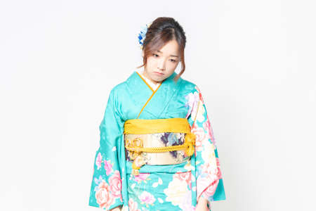 A woman in furisode standing in front of a white background and posing depressed