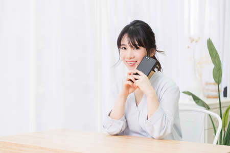 Young woman using a smartphone in the room