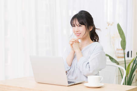 A young woman making a request gesture while using a laptop in the room