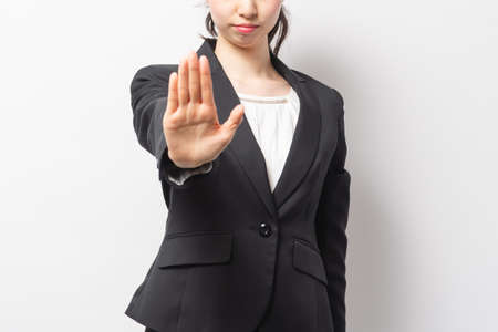 Business woman making an NG gesture in front of a white background