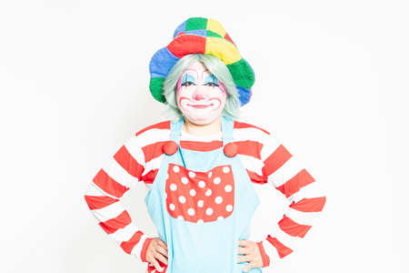 A clown who puts his hand on his waist in front of a white background Reklamní fotografie