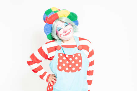 A clown who puts his hand on his waist in front of a white background