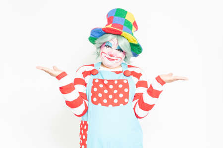 Clown making a guiding gesture in front of a white background