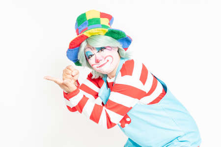 A clown standing in front of a white background and making a convincing gesture Reklamní fotografie