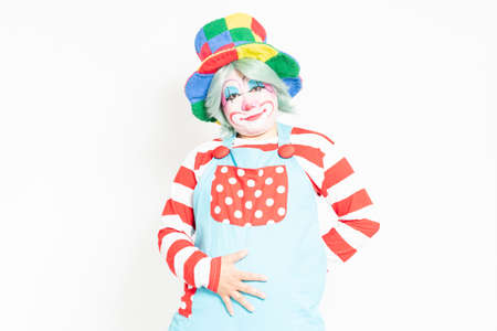 A clown standing in front of a white background and putting his hand on his stomach