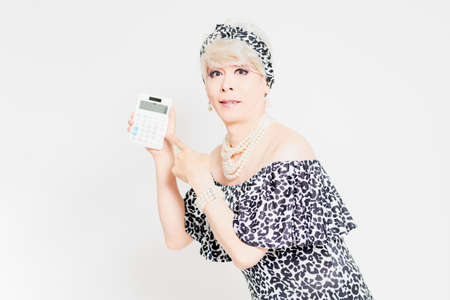 Drag queen standing in front of a white background and showing a calculator