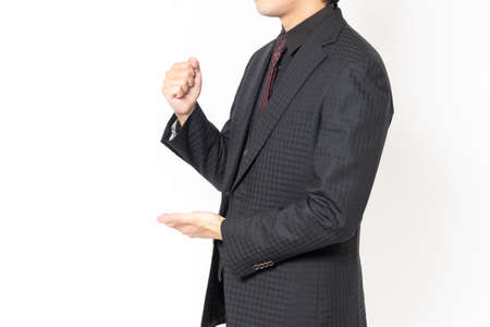 A male businessman standing in front of a white background and making a convincing gesture Foto de archivo