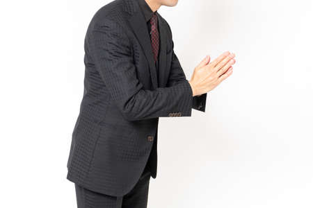 Male businessman standing in front of a white background and apologizing