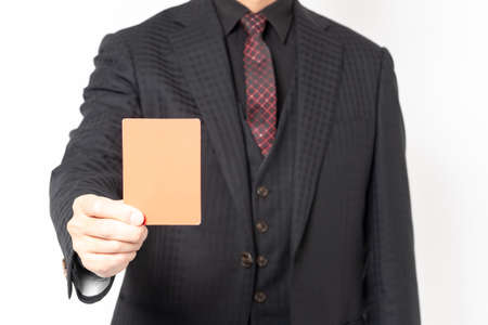 Male businessman standing in front of white background and showing red card