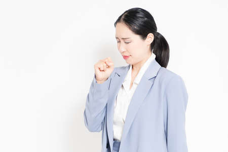 A woman standing in front of a white background and making a sore throat gesture