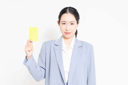 A woman standing in front of a white background and showing a yellow card