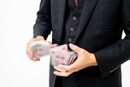 Hands of a magician playing card magic with playing cards
