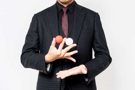 At the hands of a magician who does magic tricks with a ball