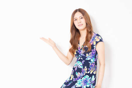 A young woman in a blue dress making a guiding gesture in front of a white wall