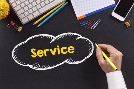 service desk: Man working on desk and writing Service