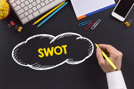 swot analysis: Man working on desk and writing SWOT Stock Photo