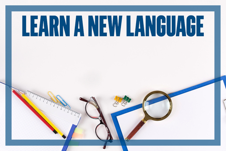 fluency: High Angle View of Various Office Supplies on Desk with a word LEARN A NEW LANGUAGE