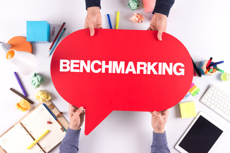 benchmarking: Two people holding speech bubble with BENCHMARKING concept