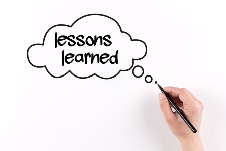 summarize: Hand writing Lessons learned on white paper, View from above
