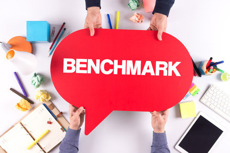 benchmark: Two people holding speech bubble with BENCHMARK concept