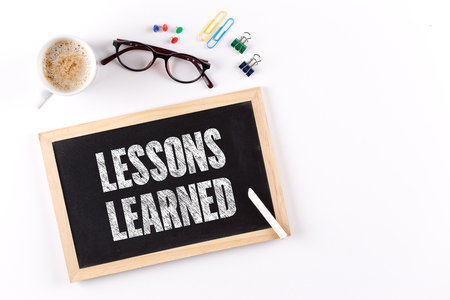 learned: LESSONS LEARNED word on Chalkboard with Coffee Cup, view from above Stock Photo
