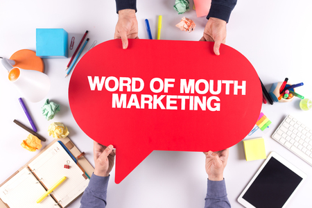 referrer: Two people holding speech bubble with WORD OF MOUTH MARKETING concept Stock Photo