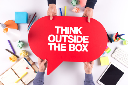 expressing artistic vision: Two people holding speech bubble with THINK OUTSIDE THE BOX concept