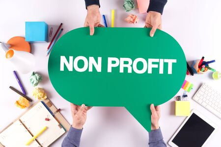 non profit: Two people holding speech bubble with NON PROFIT concept Stock Photo