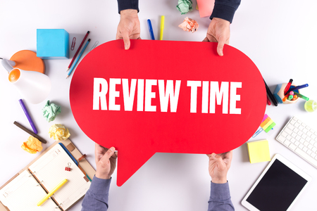 reassessment: Two people holding speech bubble with REVIEW TIME concept Stock Photo